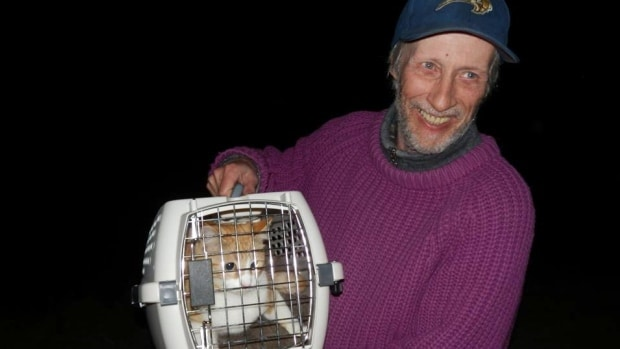 Bill Backhall holds his cat after it was rescued from a high voltage power pole. (Brenda Engel/Similkameen News Leader)