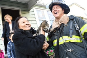 Lam and her cat, Louisa, thank an FDNY firefighter.Photo: Paul Martinka