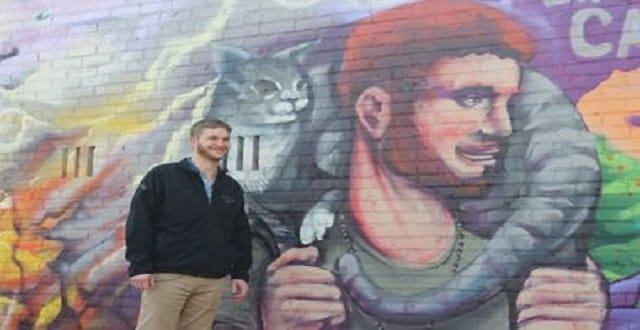 Wes King poses next to the mural in the Bongo Room parking lot. [DNAinfo/Josh McGhee]
