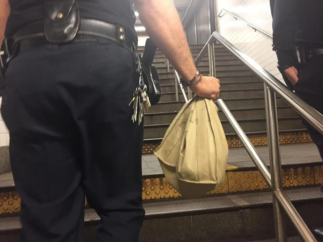 """""""Seven"""" is carried out of the station by a police officer. (DANNY LEWIS/NEW YORK DAILY NEWS)"""